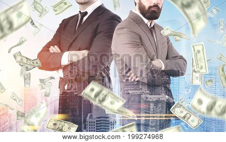 Close up of two unrecognizable young businessmen standing back to back against a cityscape background under a dollar rain. Toned image double exposure