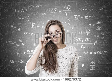 Young woman with dark long hair is wearing a white sweater and holding her glasses with a thick frame. She is looking to the distance while standing near a blackboard with formulas on it.