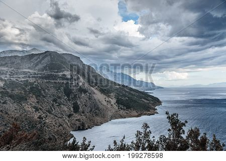 Dark stormy sky, sea waves and mountains. Dramatic landscape.