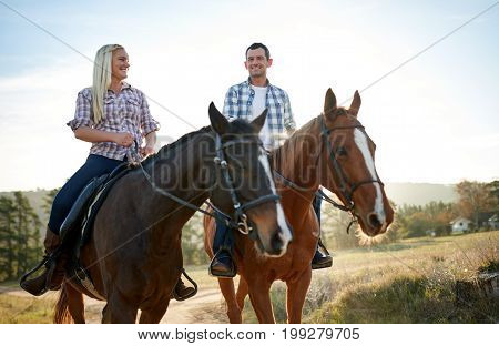 Smiling Couple Horseback Riding Together In The Countryside