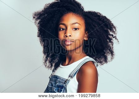 Young African With Curly Hair Standing Against A Gray Background