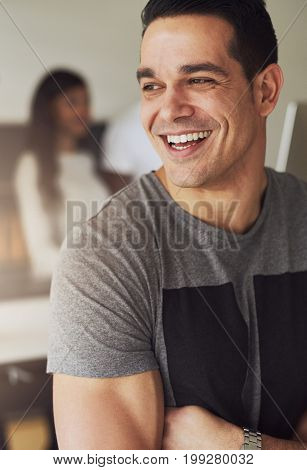 Vertical portrait of a businessman standing with arms crossed and looking away in the office.