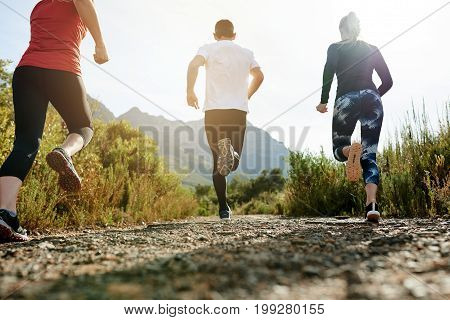 Group Of Friends Running Down A Trail Together In Nature
