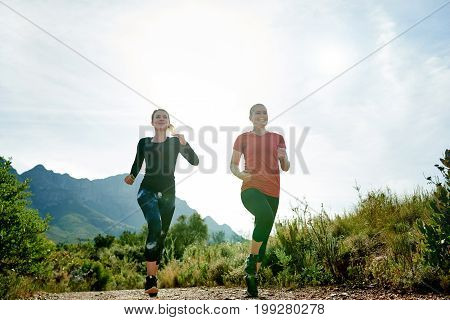 Two Smiling Female Friends Trail Running Together In The Countryside