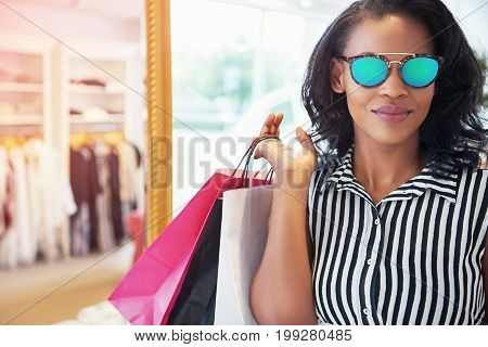 Trendy young African women shopping in a clothing boutique posing for the camera with her bags of purchases over her shoulder