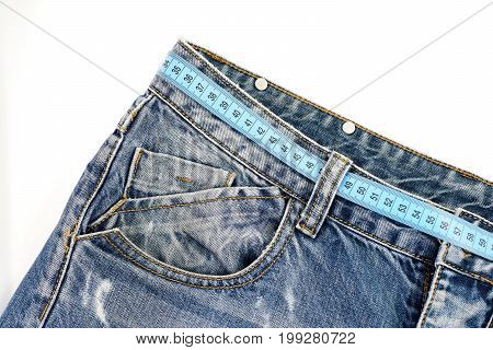 Jeans with blue measure tape instead of belt. Healthy lifestyle and dieting concept. Close up of jeans belt loops and pocket. Top part of denim trousers isolated on white background.