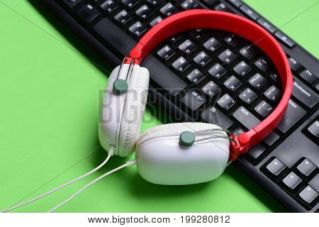 Earphones In Red And White Colors With Computer Keyboard