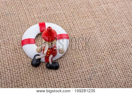 Wooden Pinocchio Doll Tied To A Life Saver
