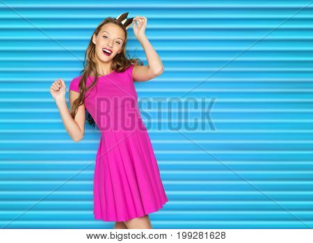 people, holidays and fashion concept - happy young woman or teen girl in pink dress and princess crown over blue ribbed background