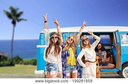 summer holidays, road trip, travel and people concept - happy young hippie friends showing peace hand sign and posing at minivan car over tropical beach background