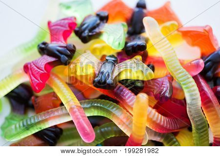 halloween, junk food and confectionery concept concept - heap of multicolored gummy worms and bet candies