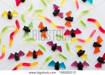 halloween, junk food and confectionery concept concept - multicolored gummy worms and bet candies over white background