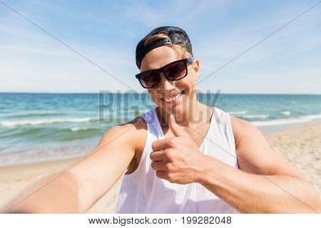 summer holidays, gesture and people concept - happy smiling young man in sunglasses and hat taking selfie and showing thumbs up on beach