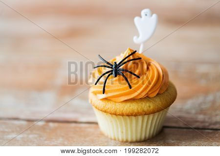 food, baking and holidays concept - cupcake or muffin with halloween party decorations on wooden table