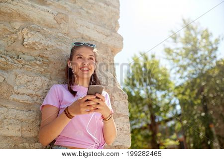 technology, lifestyle and people concept - smiling young woman or teenage girl with smartphone and earphones listening to music outdoors