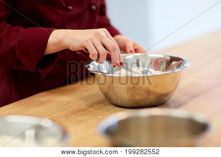 cooking food, baking and people concept - chef with flour in bowl making batter or dough