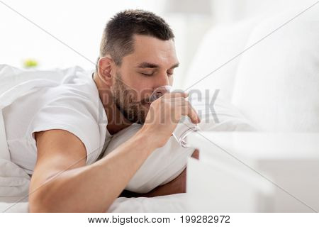people, bedtime and rest concept - man in bed drinking from glass of water at home