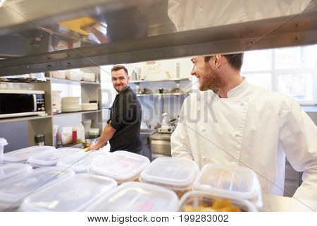 cooking food, profession and people concept - happy male chef and cook at restaurant kitchen