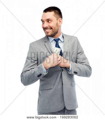 business, people and finances concept - smiling businessman hiding american dollar money into jacket pocket
