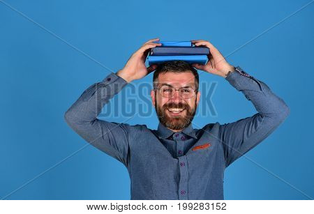 Man With Happy Face, Glasses, Beard And Books On Head