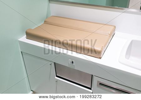 baby changing light brown diapers in public toilet