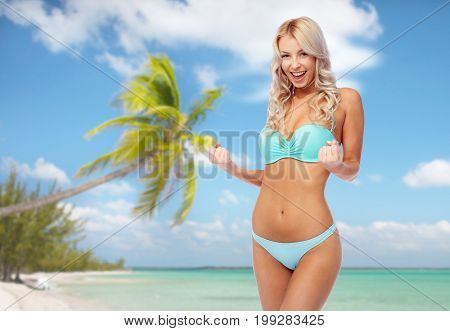 people, travel and summer holidays concept - happy smiling young woman in bikini swimsuit doing fist pump gesture over exotic tropical beach with palm trees background