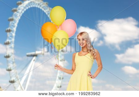 people, entertainment and summer concept - happy young woman or teen girl in yellow dress with helium air balloons over ferris wheel and sky background