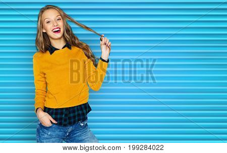 people, hairstyle and fashion concept - happy young woman or teen girl in casual clothes holding her hair strand over blue ribbed background