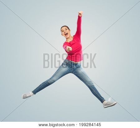 happiness, freedom, motion and people concept - smiling young woman jumping in air and pointing finger to you over blue background