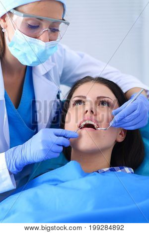 Woman dentist working at her patients teeth .