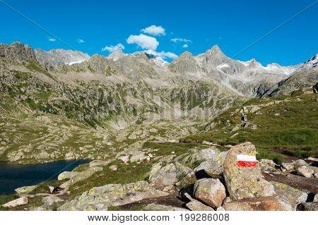 Trail sign along mountain trail. Lake Cornisello, Brenta Dolomites in Italy.