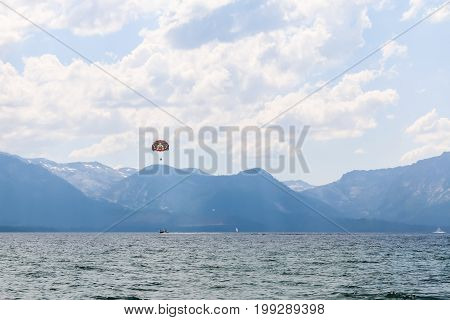 Parasailing on the Lake With Bright Sunlight and Mountains in the Background