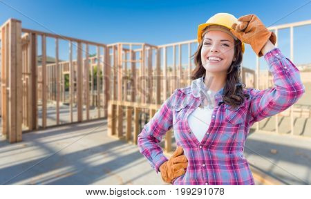Young Attractive Female Construction Worker Wearing Gloves, Hard Hat and Protective Goggles At Construction Site.