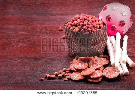 Dog snack dog chews dog biscuits on a grey wooden table wall background with copy space .
