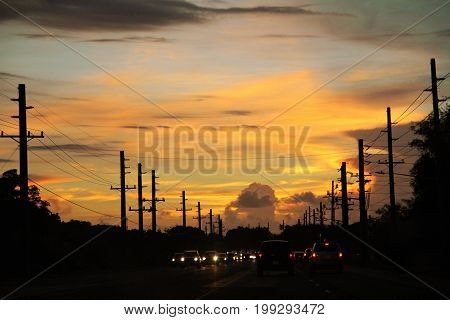 Silhouettes of cars and power posts at a busy street on Guam at sunset
