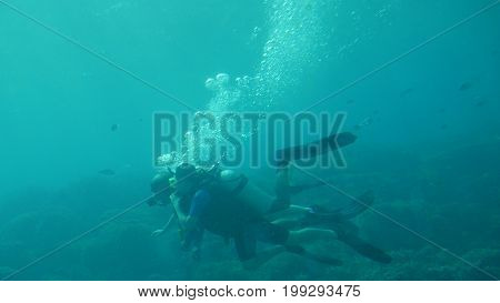 GUAM, USA--Wide shot of divers exploring the underwater wonders at the Fish Eye Marine Park, an underwater observatory which is one of the top attractions on Guam. Photo taken in December 2016.