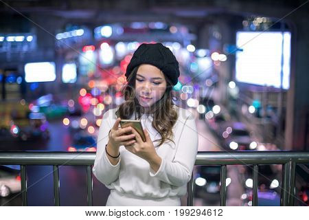 Outdoor portrait of beautiful young asian woman using her mobile phone at night.