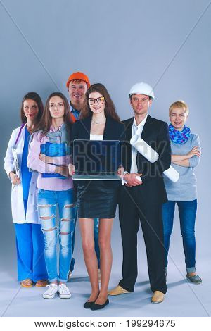 Smiling businesswoman with laptop and group of industrial workers.