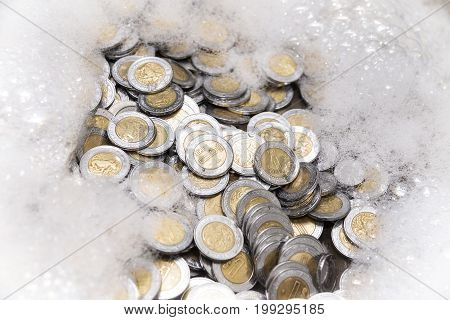 conceptual image of money laundering mexican pesos coins with soap foam