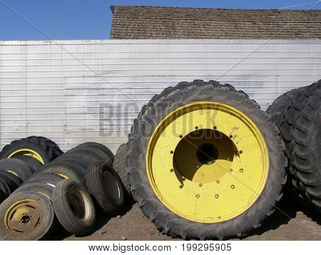 Farm tractor tires leaning on shed wall