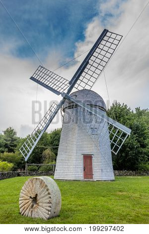 White Windmill with red door next to a stone wheel in Jamestown Rhode Island