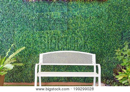 A white bench on artificial grass and ornamental plants on artificial plants wall background.