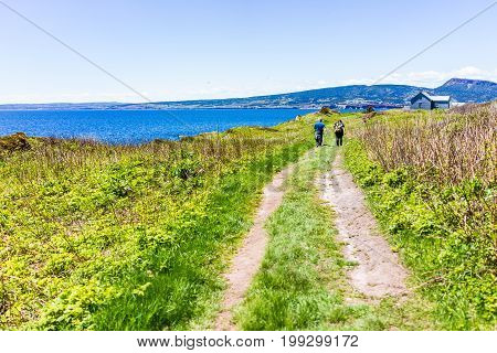 Perce Canada - June 6 2017: People couple walking on trail by ocean cliff coast on Bonaventure Island in Quebec Canada by Gaspesie Gaspe region