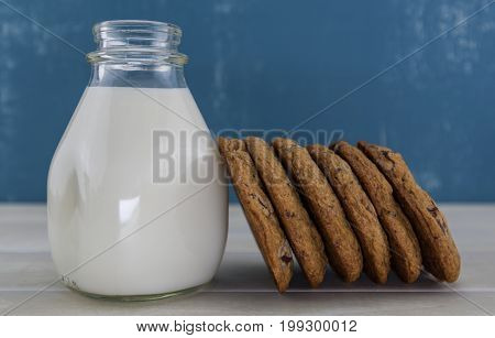 Six Cookies Leaning Against Jar Of Milk