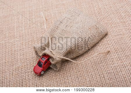 Red Toy Car Out Of A Linen Sack On A Canvas