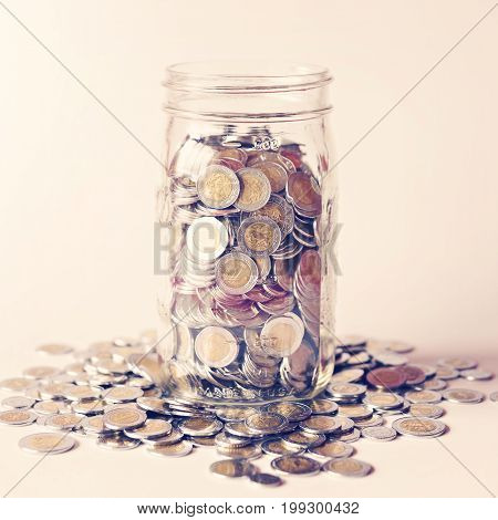 glass jar with full of mexican pesos coins with vintage color tone process