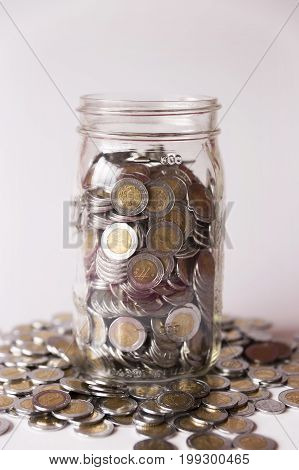 glass jar with many mexican pesos coins