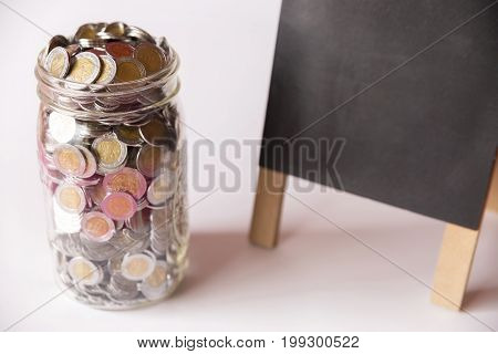 glass jar with full of mexican pesos coins and chalk board