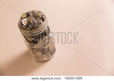 mexican pesos coins in glass jar with copy space