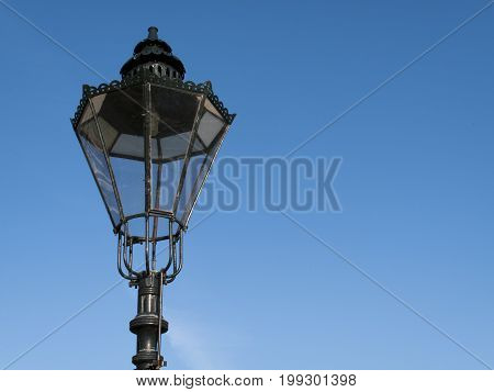 Period styled cast iron streetlamp against a clear blue sky